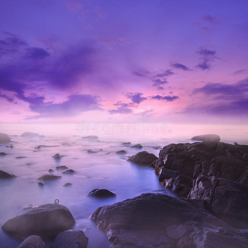 Puesta del sol rosada y púrpura sobre Misty Rocks en el mar fotografía de archivo