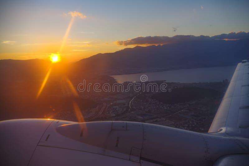 Puesta del sol sangrienta fuera de la ventana del avión imagen de archivo
