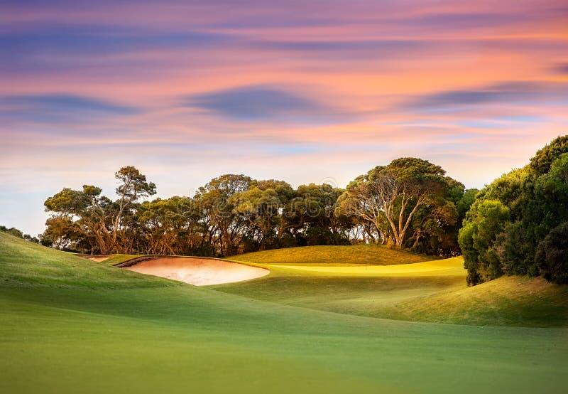 Puesta del sol sobre campo de golf imagenes de archivo
