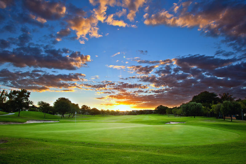 Puesta del sol sobre campo de golf foto de archivo libre de regalías