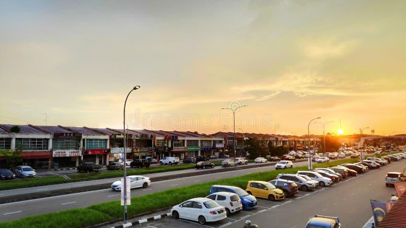 Puesta del sol sobre casas y el coche ordinarios de la tienda sobre Johor Bahru en Malasia imagen de archivo libre de regalías
