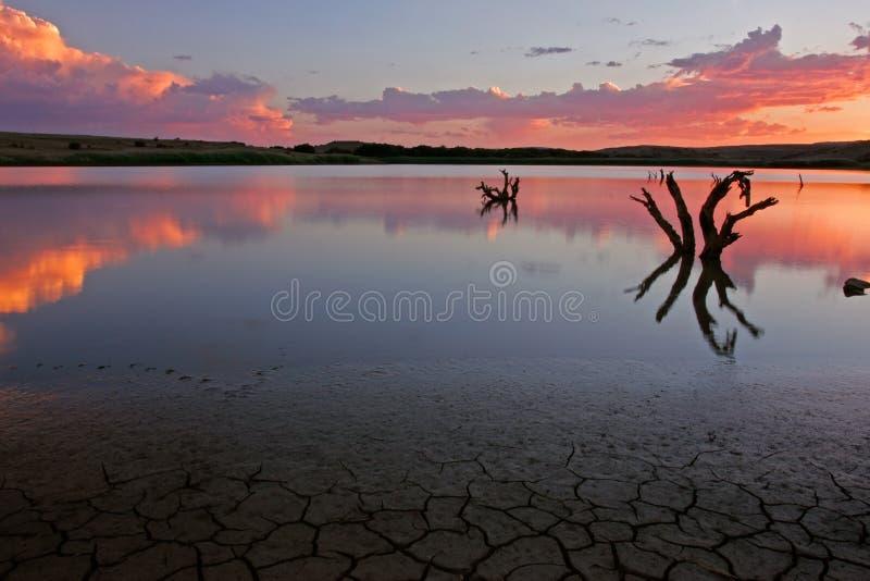 Puesta del sol sobre el agua imagenes de archivo