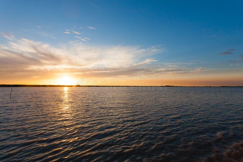 Puesta del sol sobre el agua foto de archivo