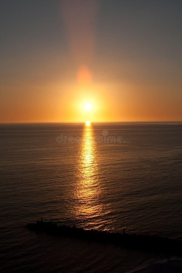 Puesta del sol sobre el agua con la rotura de la onda fotografía de archivo