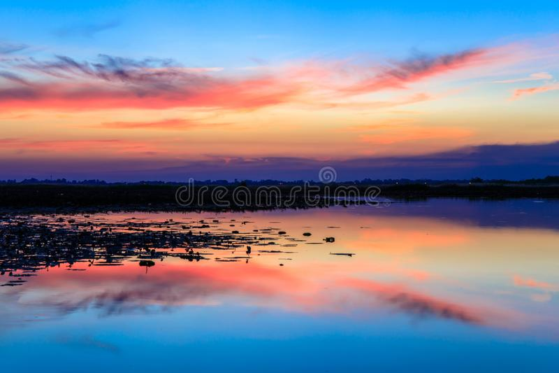 Puesta del sol sobre el agua del lago con el cielo azul dramático imagenes de archivo