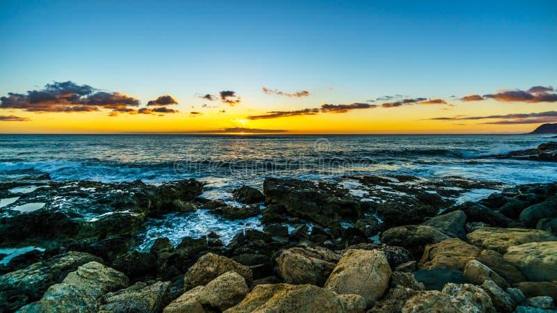 Puesta del sol sobre el horizonte con algunas nubes y las orillas rocosas de la costa oeste de Oahu fotografía de archivo libre de regalías