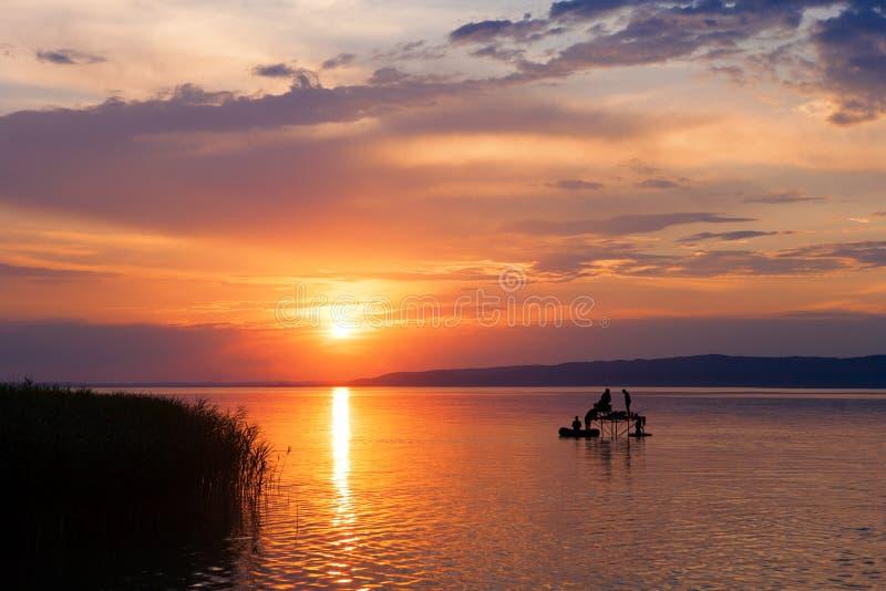 Puesta del sol sobre el lago Balatón con las siluetas del ` de los pescadores en Hungría fotos de archivo