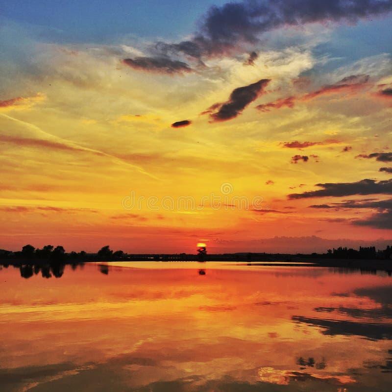 Puesta del sol sobre el lago tranquilo fotos de archivo