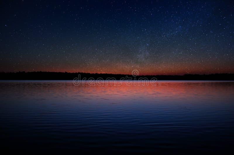 Puesta del sol sobre el lago tranquilo con las estrellas reales en cielo oscuro fotos de archivo