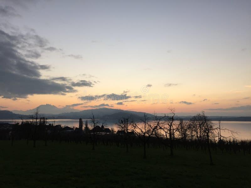 Puesta del sol sobre el lago y las montañas imagen de archivo libre de regalías