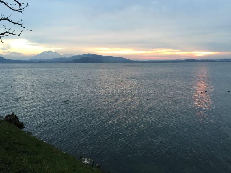 Puesta del sol sobre el lago y las montañas fotos de archivo
