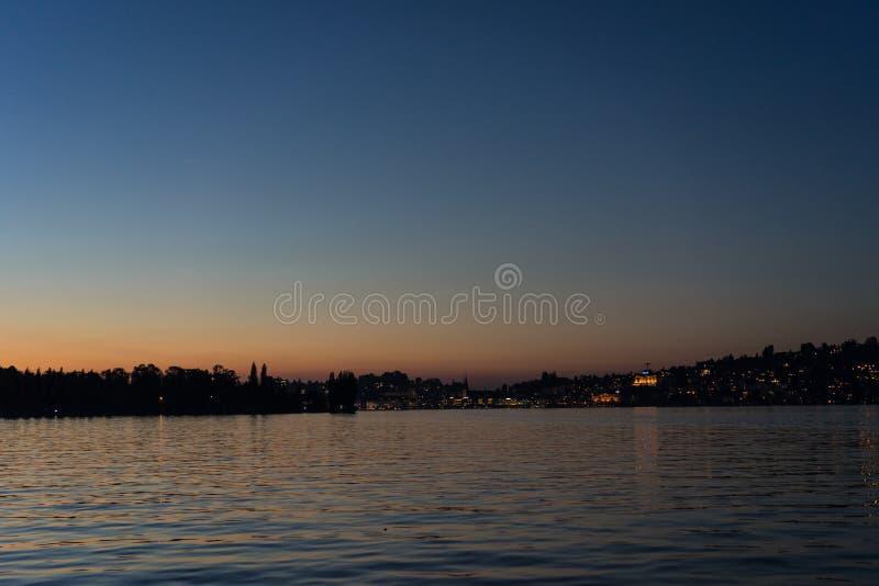 Puesta del sol sobre el lucerne del lago con agua y el cielo rojo fotografía de archivo