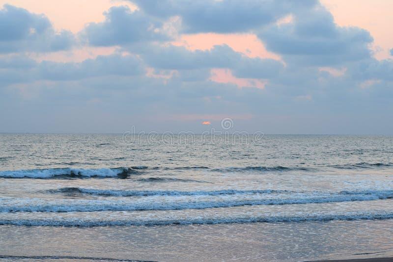 Puesta del sol sobre el mar con el cielo nublado, playa de Ladghar, Dapoli, la India fotos de archivo