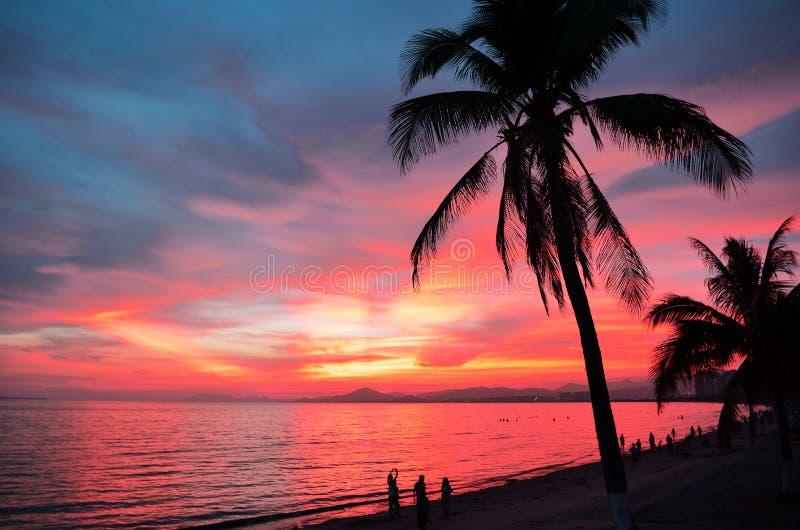 Puesta del sol sobre el mar con la silueta de palmeras y de algunos turistas en la playa en distancia Sanya, China fotos de archivo libres de regalías