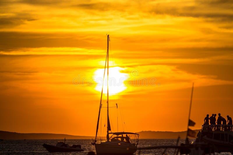 Puesta del sol sobre el mar con las siluetas de yates foto de archivo libre de regalías