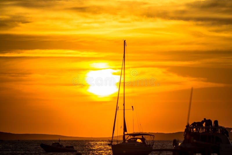 Puesta del sol sobre el mar con las siluetas de yates imagen de archivo libre de regalías