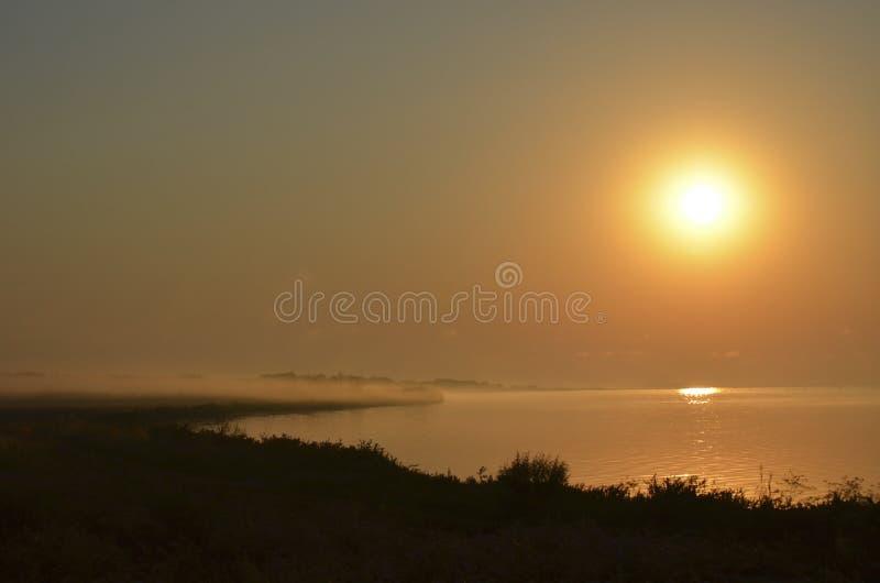 Puesta del sol sobre el mar neblina de la niebla foto de archivo libre de regalías