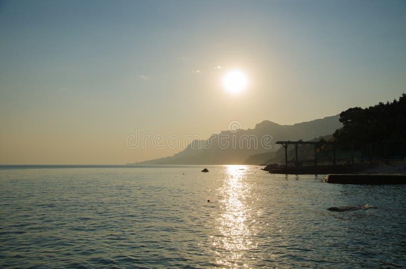 Puesta del sol sobre el mar, silueta de montañas fotos de archivo