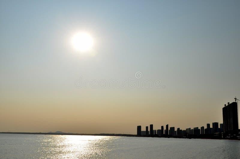 Puesta del sol sobre el mar y la ciudad foto de archivo libre de regalías