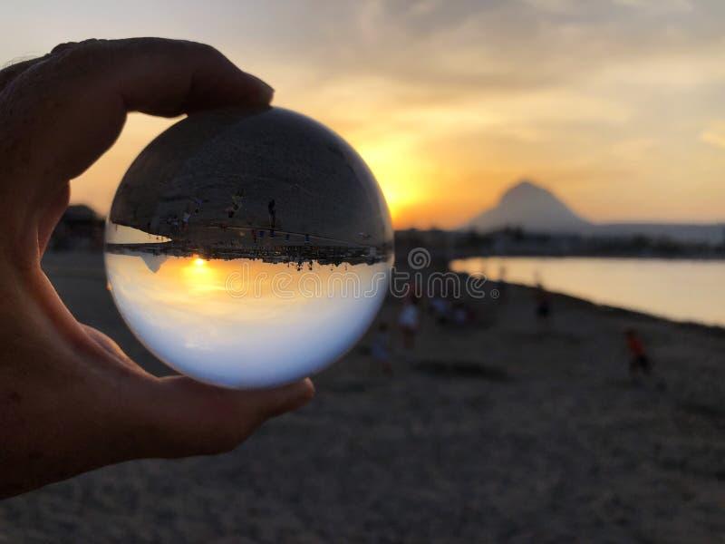 Puesta del sol sobre el mar y la playa con una bola de cristal fotografía de archivo