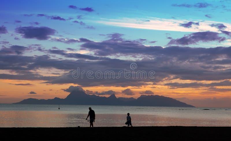Puesta del sol sobre el mar y las montañas, la silueta del pescador en tierra tahití imagen de archivo libre de regalías