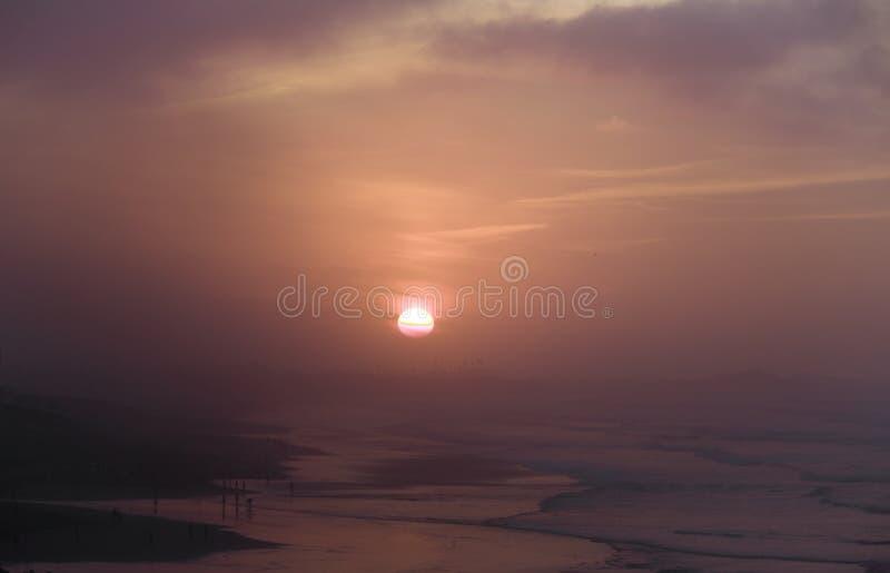 Puesta del sol sobre el Océano Atlántico en niebla de la tarde imagen de archivo