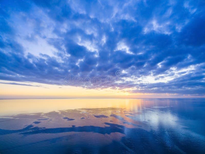 Puesta del sol sobre el océano - cielo nublado azul, sol, y agua lisa fotografía de archivo libre de regalías