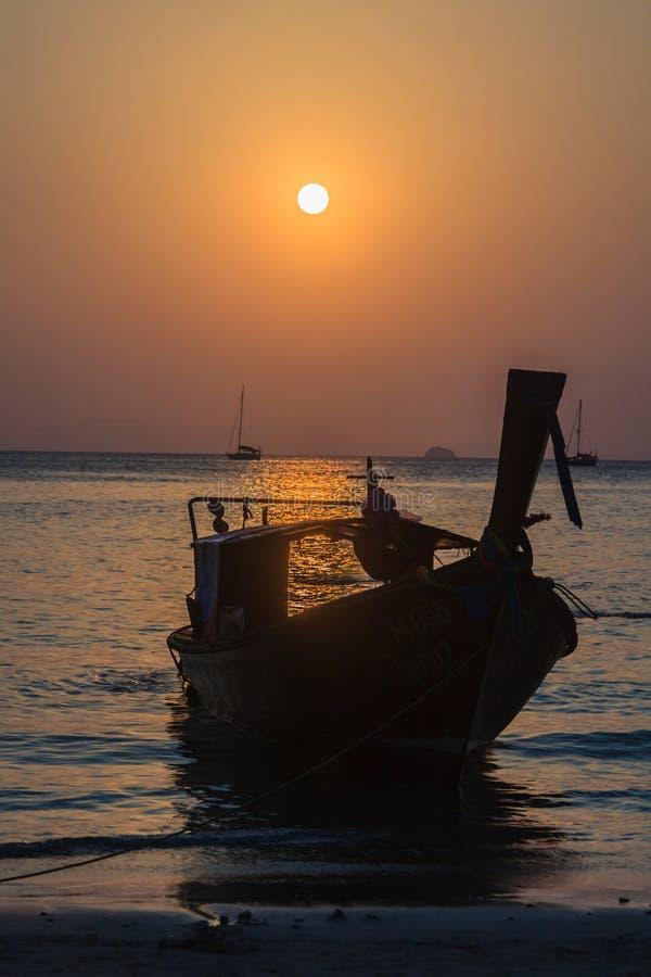 Puesta del sol sobre el océano con el barco de navegación en contraluz imagenes de archivo