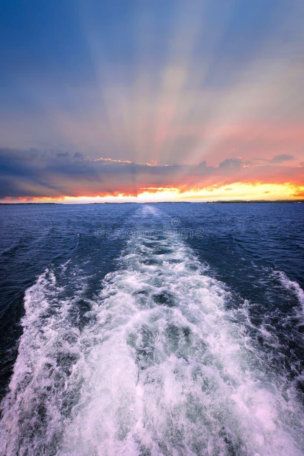 Puesta del sol sobre el océano con estela del barco imágenes de archivo libres de regalías