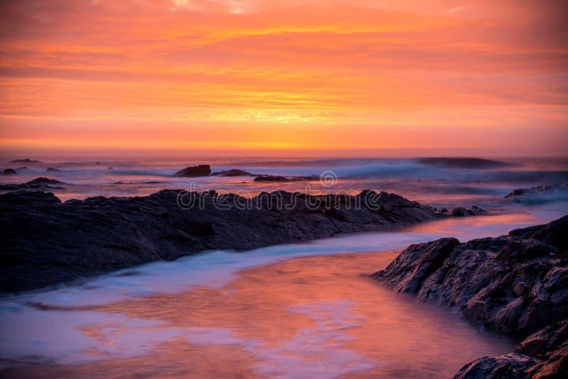 Puesta del sol sobre el océano, rocas y ondas foto de archivo