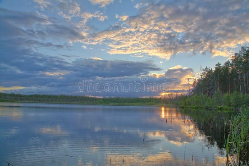 Puesta del sol sobre el pequeño lago del bosque fotos de archivo libres de regalías