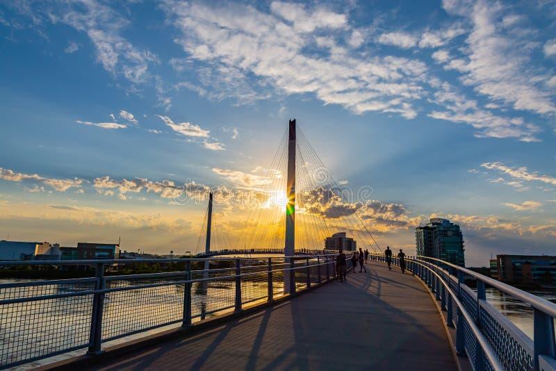 Puesta del sol sobre el puente de Bob Kerrey Pedestrian y el río Missouri hinchado en Omaha Riverfront foto de archivo
