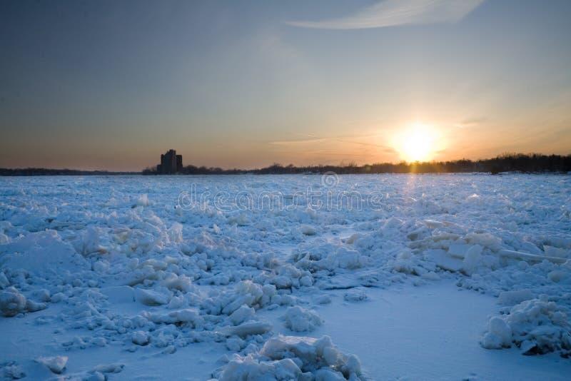Puesta del sol sobre el río congelado fotografía de archivo