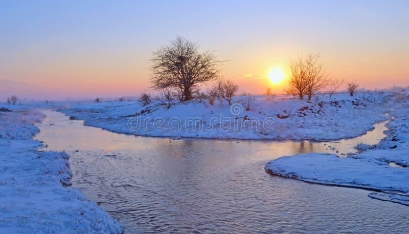 Puesta del sol sobre el río del invierno imagenes de archivo