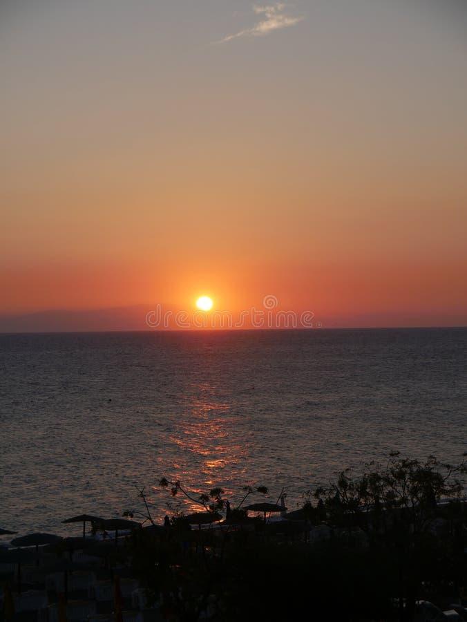 Puesta del sol sobre Ellie Beach que es la playa más cercana a Rhodes Town y es popular entre los locals y los turistas igualment imagen de archivo
