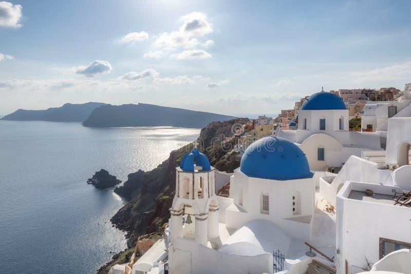Puesta del sol sobre iglesias abovedadas azules en la caldera en Oia en la isla griega de Santorini foto de archivo libre de regalías