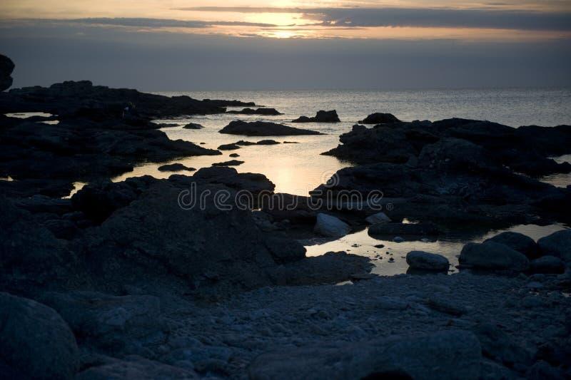 Puesta del sol sobre línea de la playa rocosa imagenes de archivo