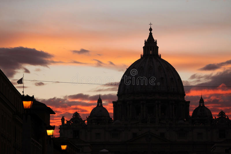 Puesta del sol sobre la bóveda de la basílica de San Pedro en la Ciudad del Vaticano i fotografía de archivo
