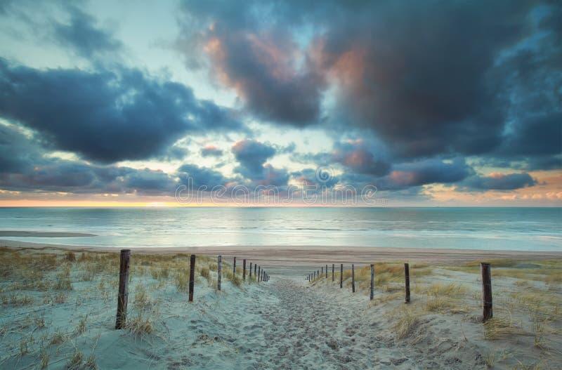Puesta del sol sobre la playa de Mar del Norte y la trayectoria de la arena en las dunas fotos de archivo libres de regalías