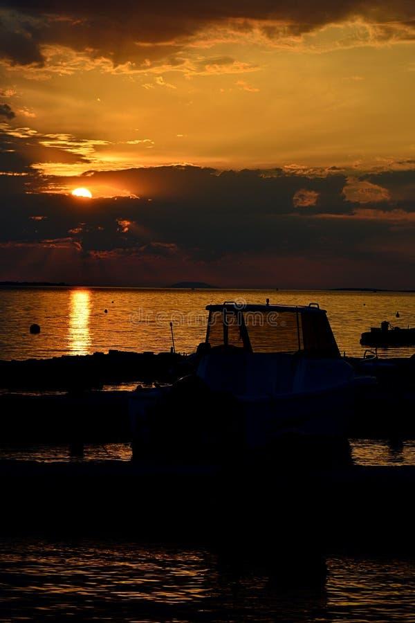 Puesta del sol sobre la playa de Vrsi Mulo en Croacia, Adriático con la silueta de barcos y de molos fotografía de archivo