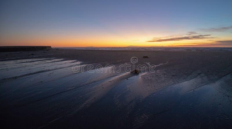 Puesta del sol sobre la salida de marea de Santa Clara River al Océano Pacífico en el parque de estado de McGrath en la costa de  fotos de archivo