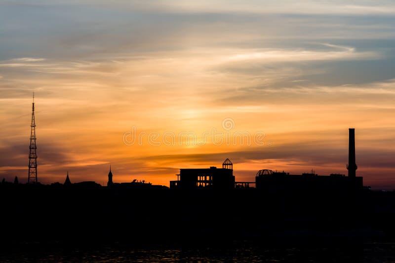 Puesta del sol sobre la silueta de la ciudad cerca del agua foto de archivo libre de regalías