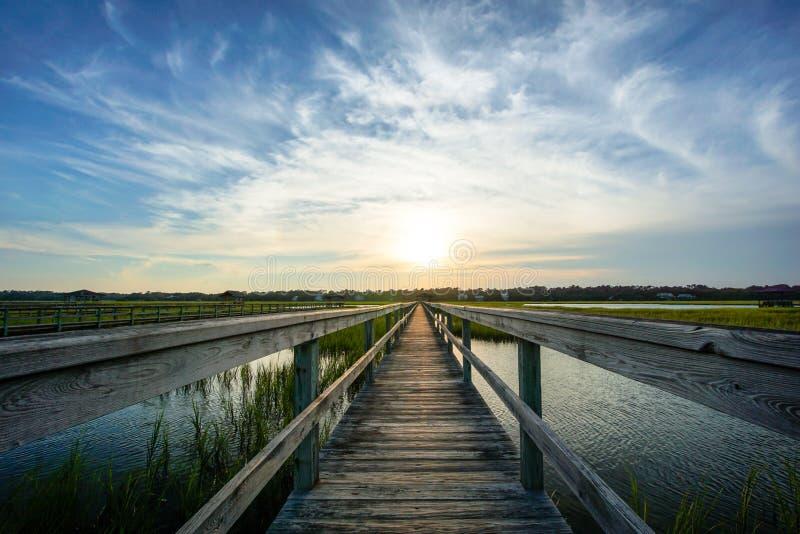 Puesta del sol sobre las aguas costeras con un paseo marítimo de madera muy largo foto de archivo libre de regalías
