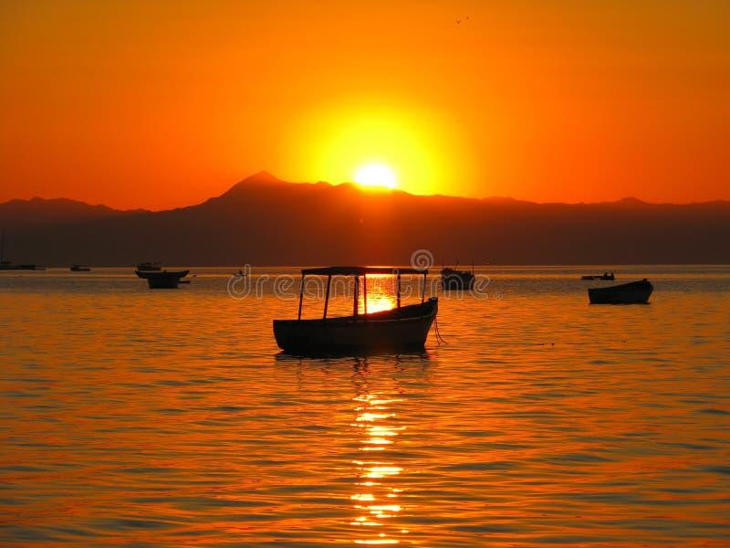 Puesta del sol sobre los barcos en el lago Malawi fotografía de archivo