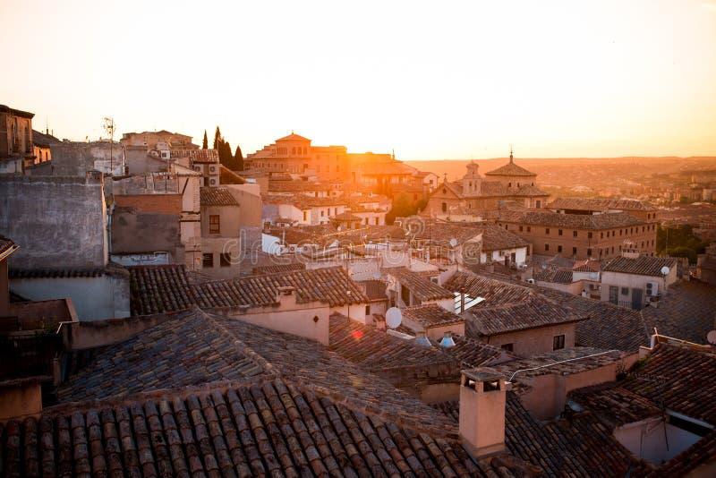 Puesta del sol sobre los tejados de casas viejas en Toledo - una ciudad antigua con arquitectura hermosa cerca de Madrid, España, fotografía de archivo