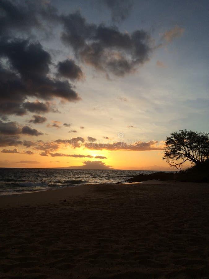 Puesta del sol sobre poca playa imagen de archivo