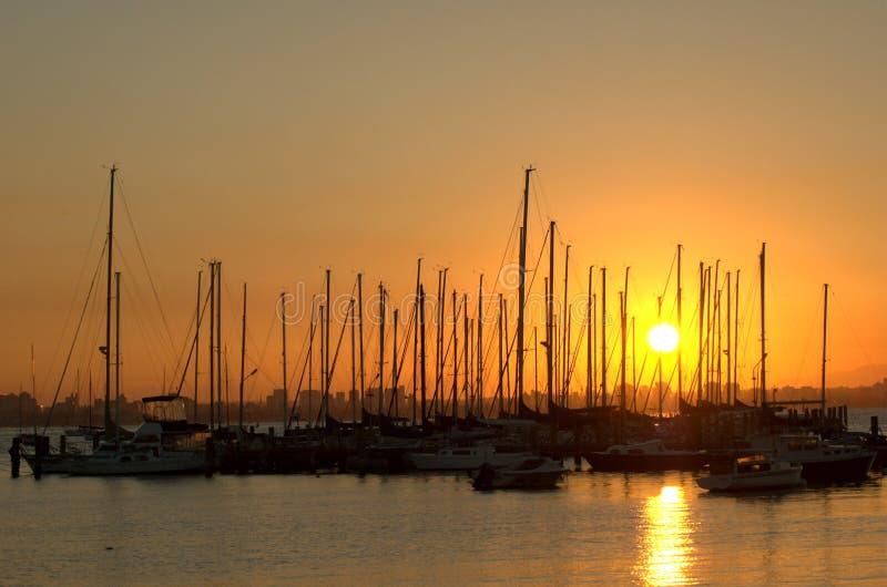 Puesta del sol sobre puerto deportivo fotografía de archivo