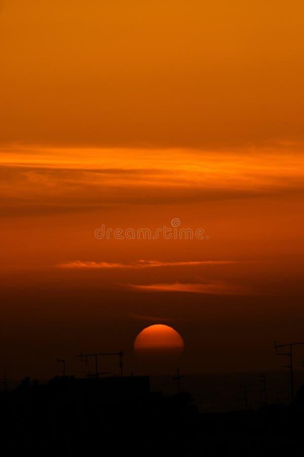 Puesta del sol sobre tejados y el mar fotografía de archivo