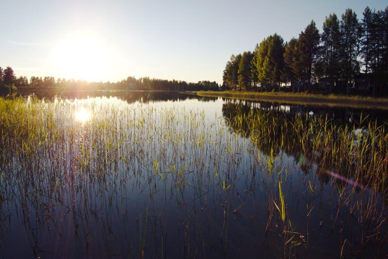 Puesta del sol sobre un lago en Gargnäs en Suecia durante el solsticio de verano imagen de archivo libre de regalías