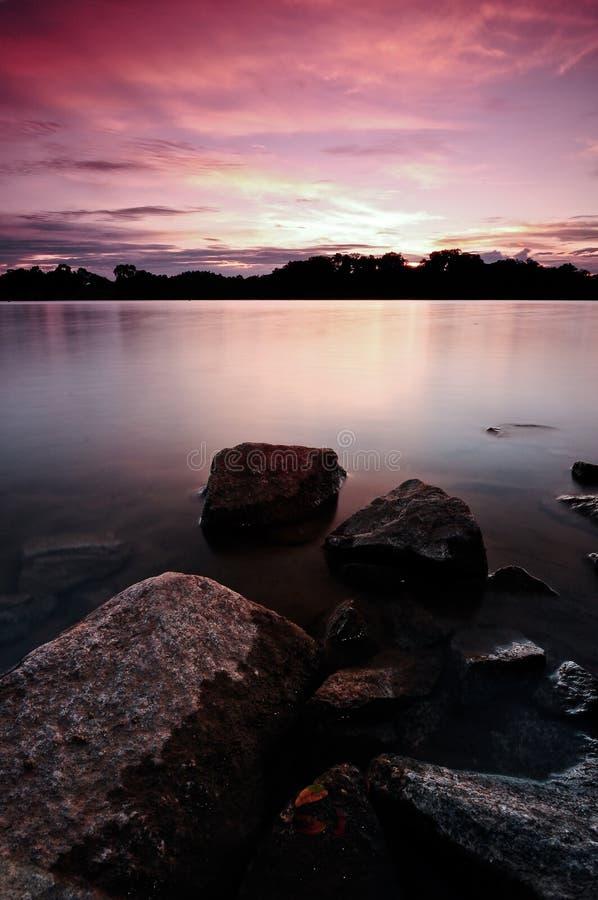 Puesta del sol sobre un lago sereno fotografía de archivo libre de regalías